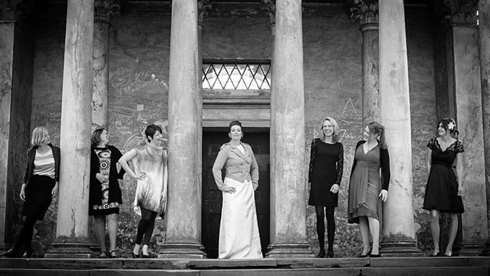 Indlæs billede 3 af 5. Bridal party posing around columns in Coppenhagen