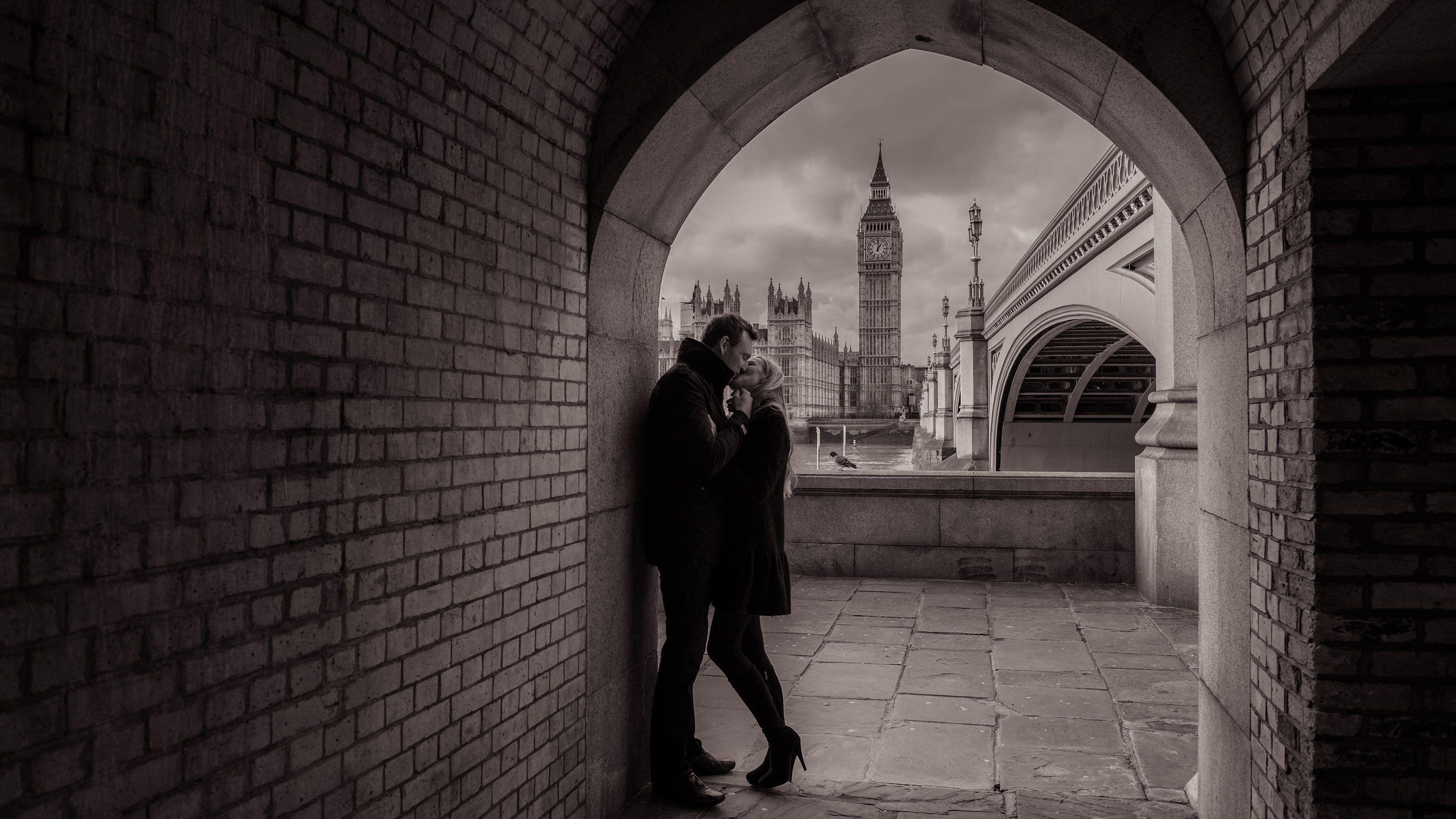 Couple kissing in an archway in London