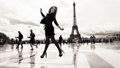 Stylish woman caught mid jump infront of the eiffel tower in paris