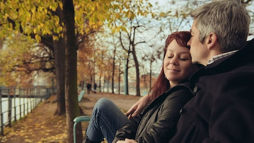 Couple sitting on a bench in a park in Paris