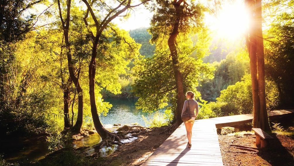 Foto 3 van 8. Sunset view of Krka Waterfalls Park with woman observing beautiful scenery.