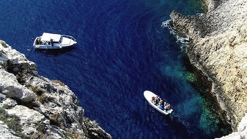 Aerial view showing two boats entering and leaving blue caves.