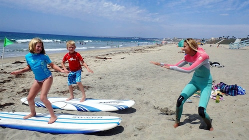 Instructor teaching children how to surf in Los Angeles