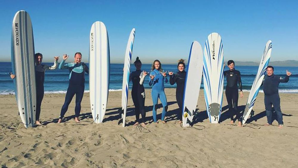 Surfers pose with surf boards on a beach in LA