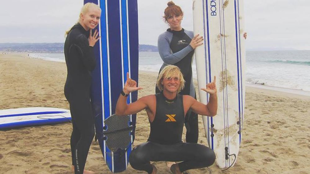 Two surfers pose with a surf instructor while holding surf boards on an LA beach