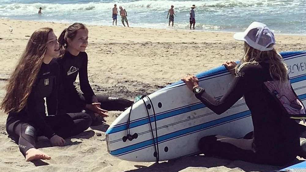 Two girls in wetsuits listen to a surf instructor who is holding a surf board on the beach
