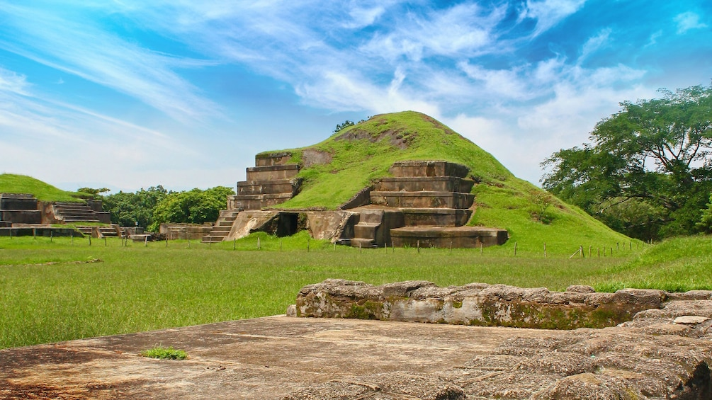 Show item 3 of 5. Mayan pyramid covered in grass