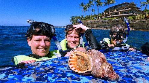 snorkelers with a large seashell in Kauai