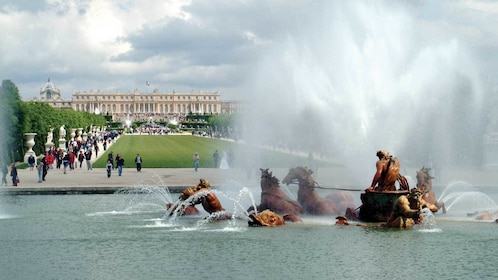 groups of visitors walking along the gardens in Versailles