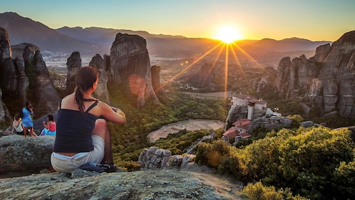 Woman perched on a rock looking out at the scenery of Meteora at sunset