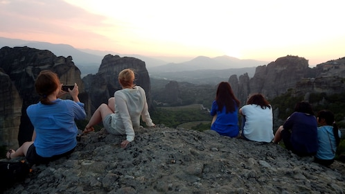 Group relaxing on a rock enjoying the view of Meteora at sunset