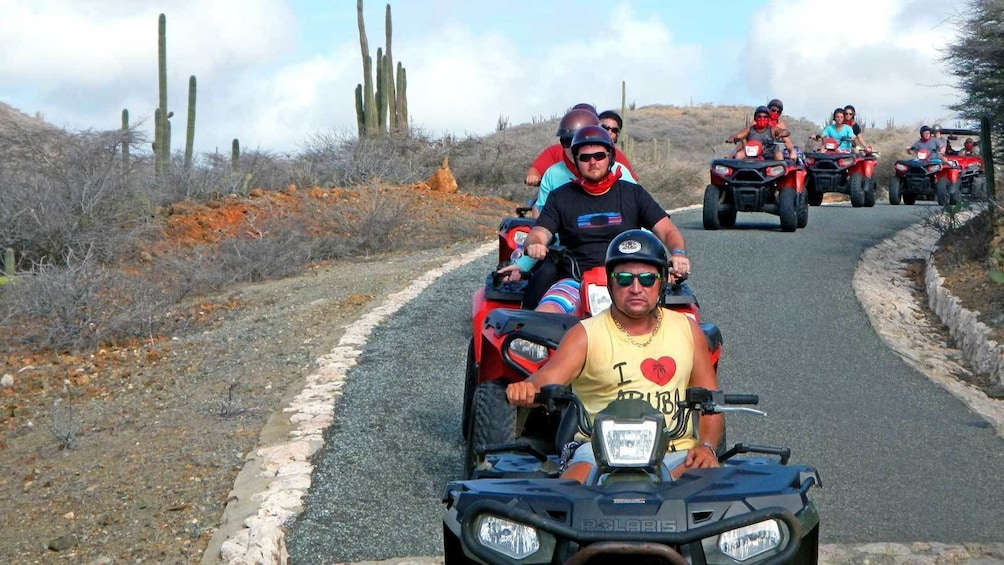 Show item 1 of 10. riding ATVs through a paved road in Aruba