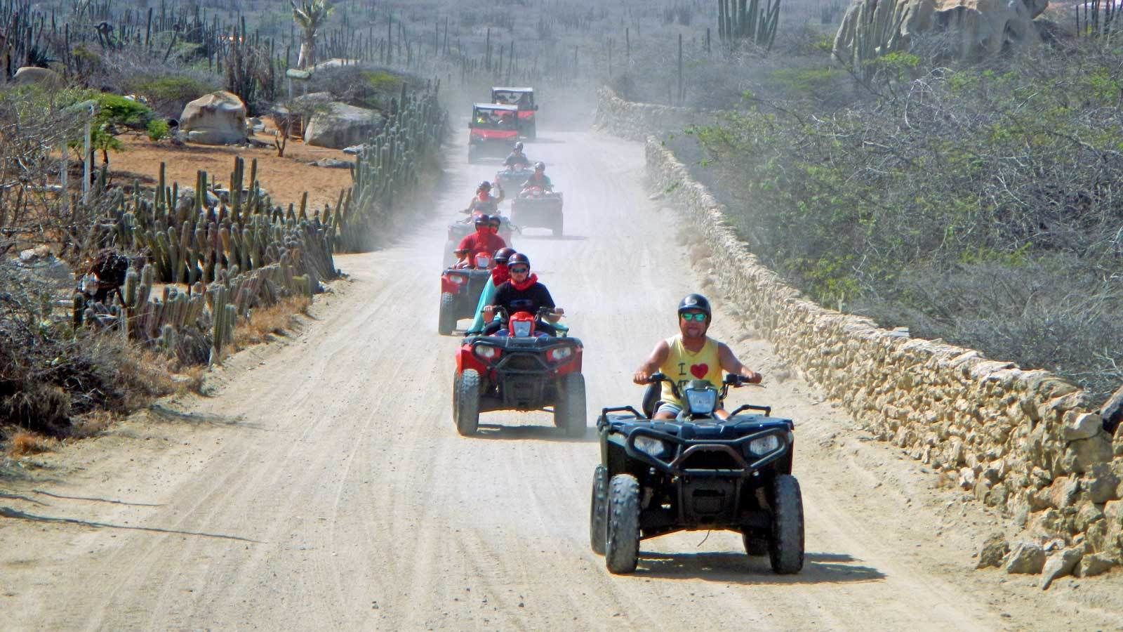 ATVs kicking up dust on a dirt road in Aruba