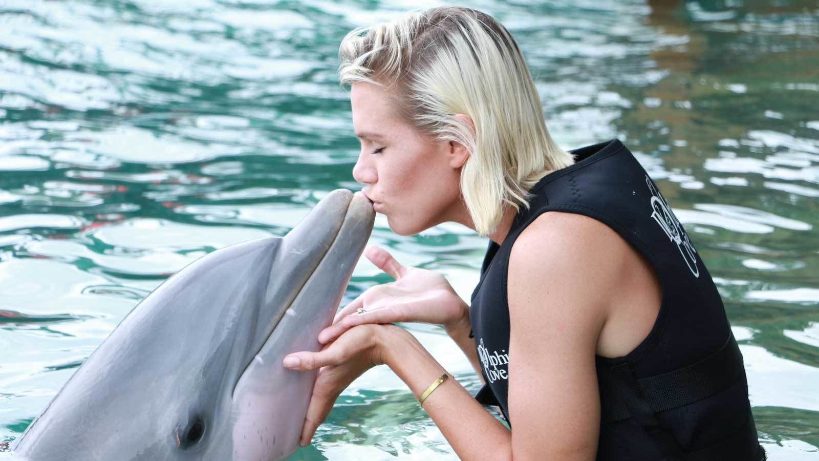 woman kissing a dolphin at the Cayman Islands