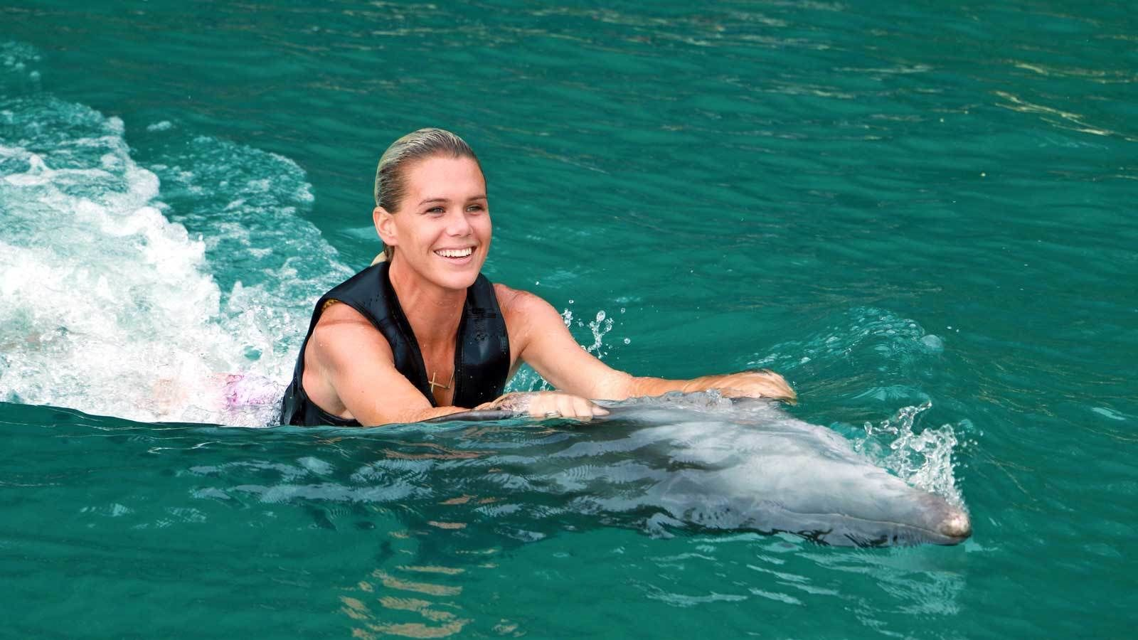 dolphin pulling woman while swimming upside down in the water at the Cayman Islands