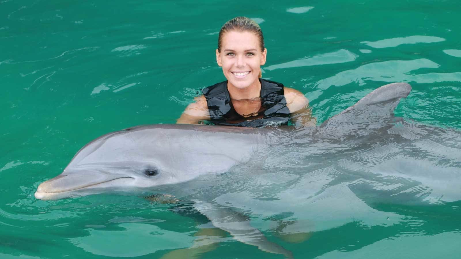 woman holding a dolphin in the water at the Cayman Islands