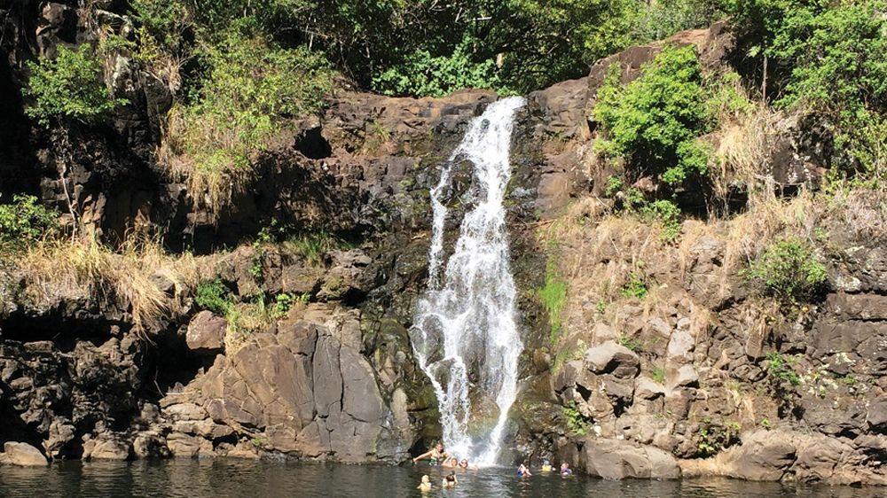 Waimea Falls with people swimming in a pool below