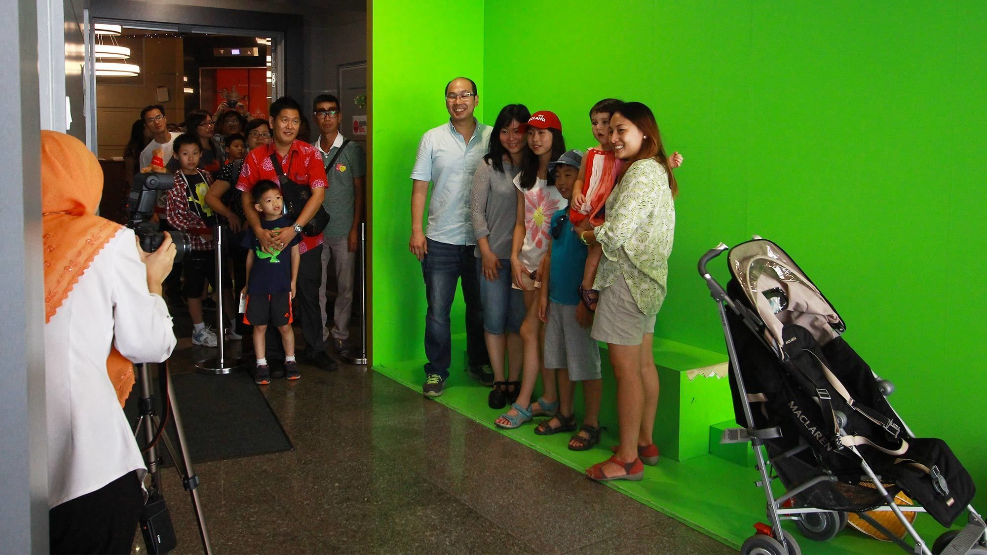 Family stands in front of green screen for photo at KL Tower in Kuala Lumpur