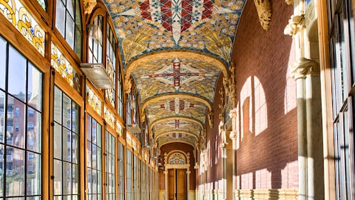 Hallway lined with windows and an ornate ceiling in a cathedral in Sant Pau