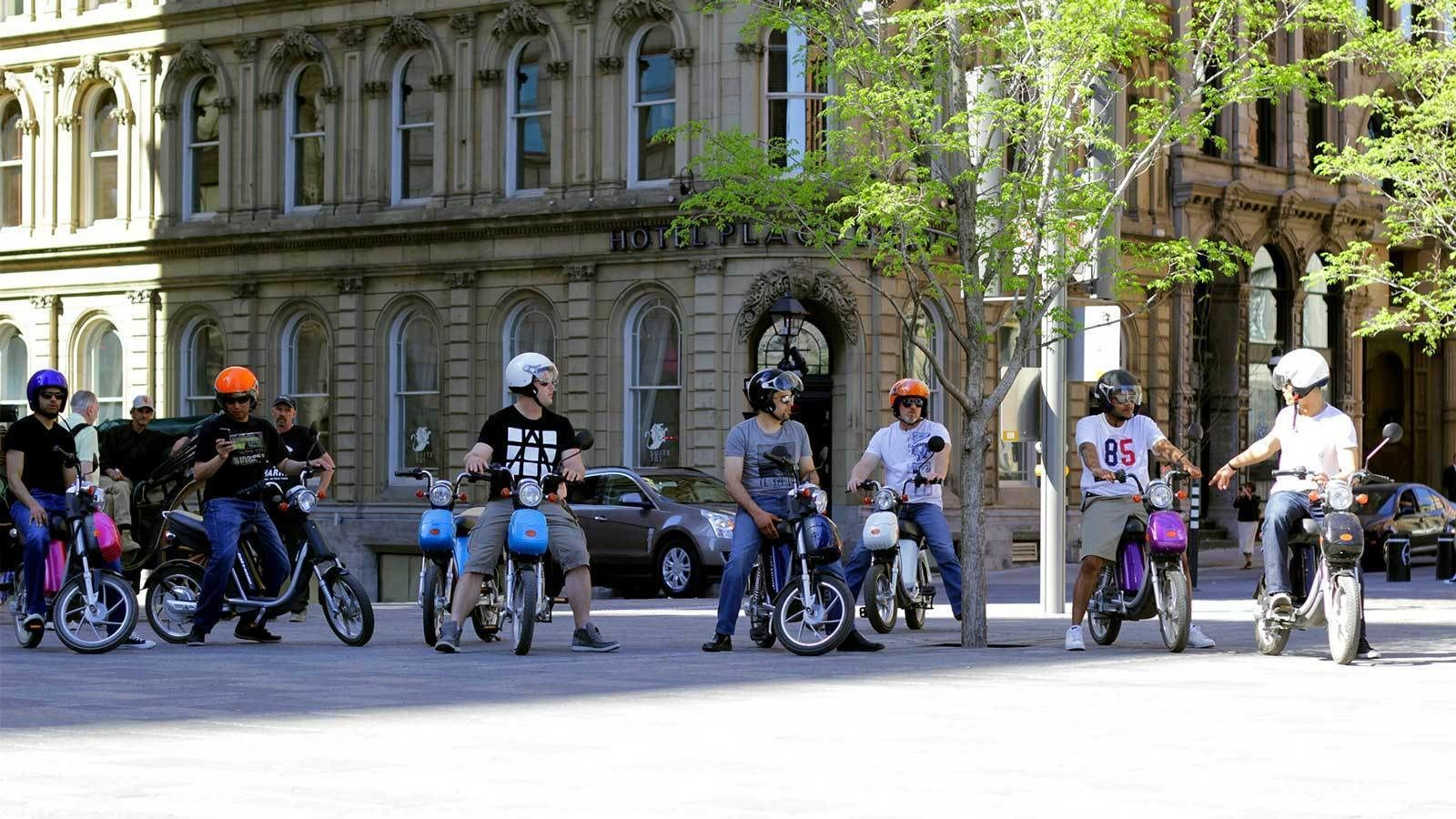 a group of scooter riders in an intersection in Montreal