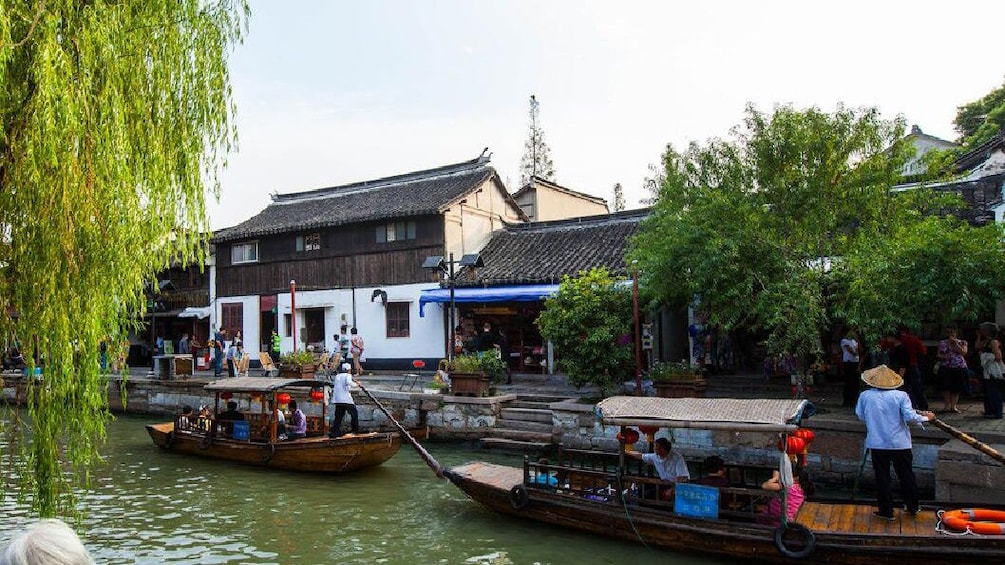 Show item 3 of 10. Two passenger pole boats are traveling down a canal in Zhujiajiao Water Town