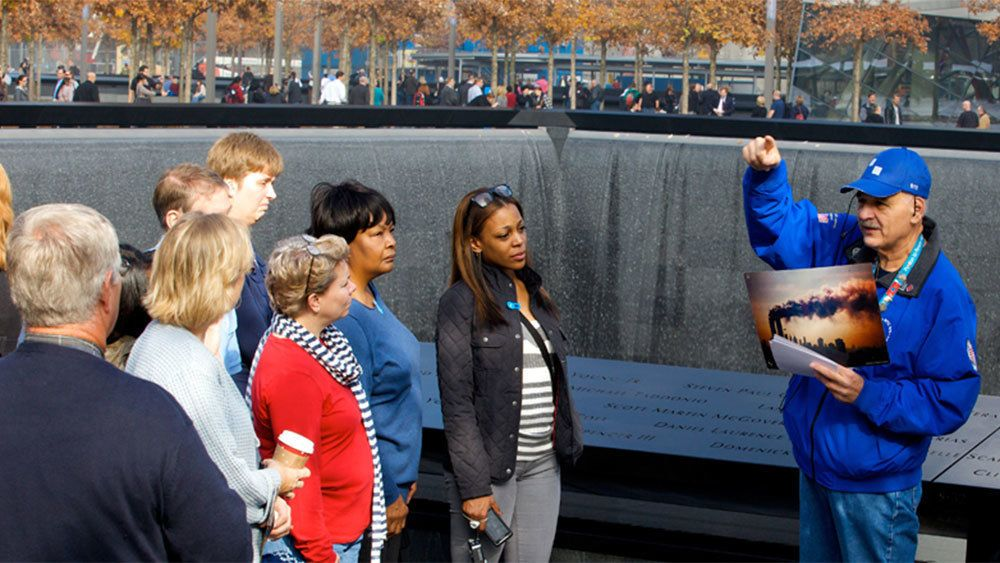 Tour guide with group at the 9/11 Memorial fountain in New York