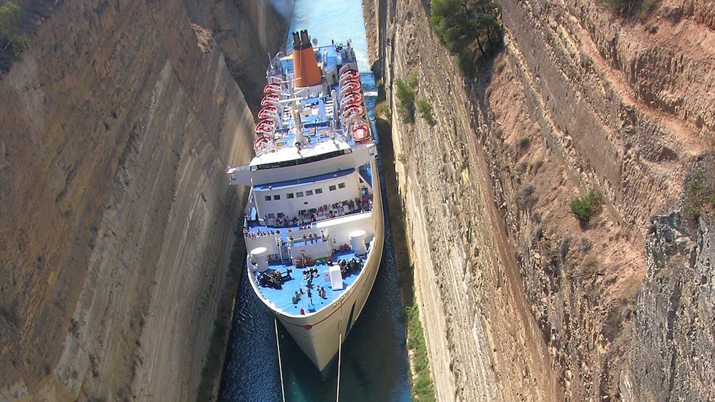 Show item 2 of 5. Birds-eye view of boat passing through narrow tunnel.
