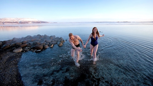 couple standing in shallow beach waters in Reykjavik