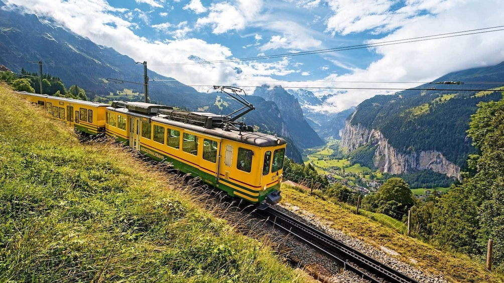 Show item 1 of 8. train running along the mountain scape in Switzerland