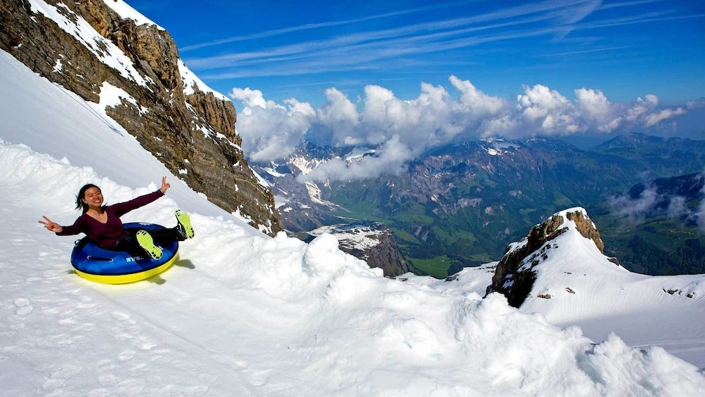 Show item 2 of 7. woman sledding down the mountain in Switzerland