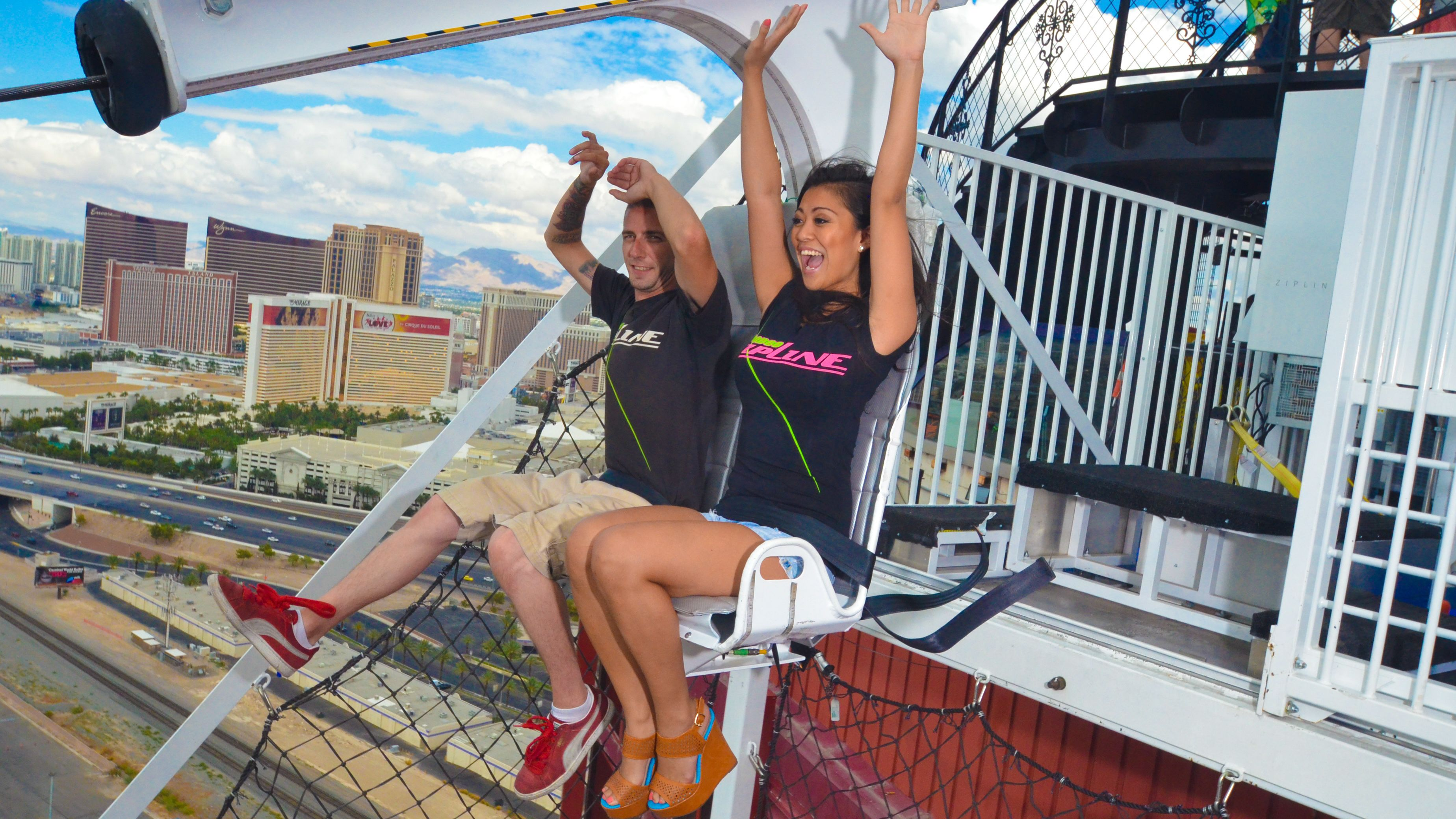 Happy tourists ziplining across Vegas strip during the day.