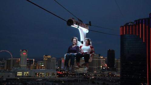 Tourists ziplining across Vegas strip at night.