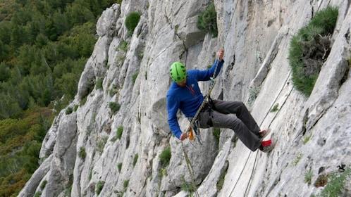 Man rappelling down a mountain in Santorini