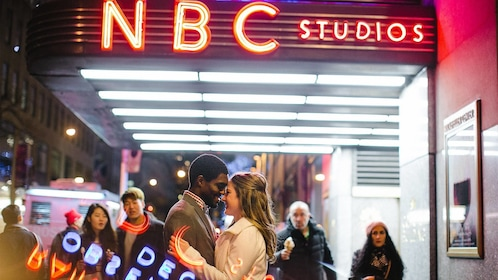 Couple standing in front of NBC Studios at night in New York