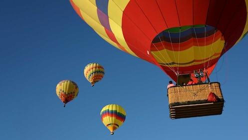 Multiple hot air balloons ascending high in Colorado Springs