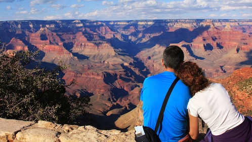 Couple sitting on the edge of the Grand Canyon