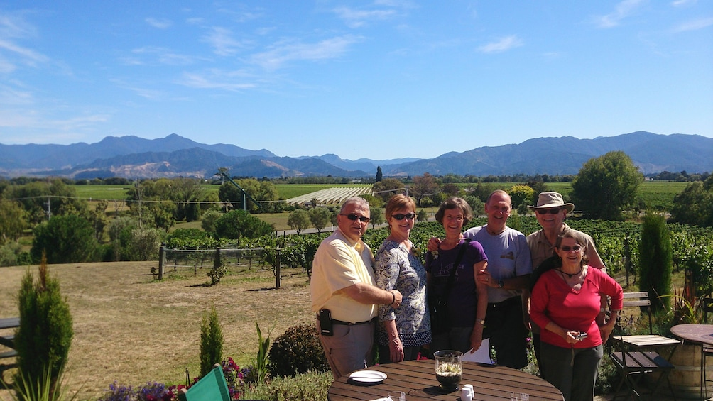 Show item 4 of 5. Group posing at outdoor patio with beautiful vineyards in the distance.