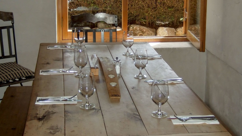 Show item 4 of 5. Rustic table and wine glasses at a vineyard in Marlborough