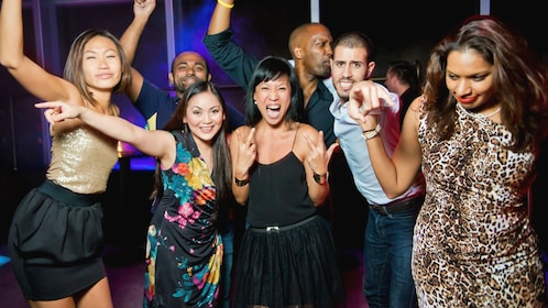 Happy group of people posing for camera in nightclub.