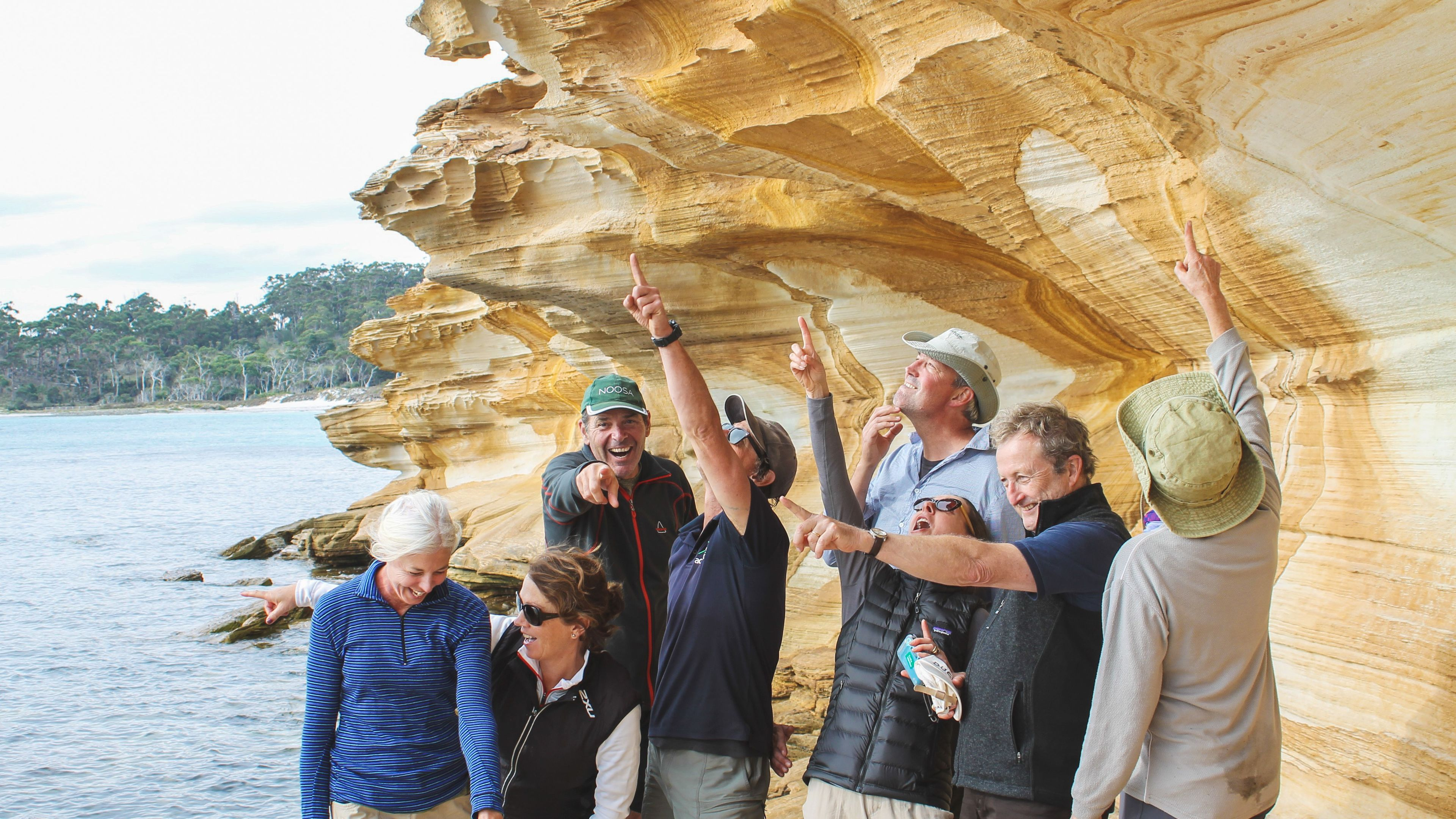 Group of tourists observing rock formations on Maria Island.