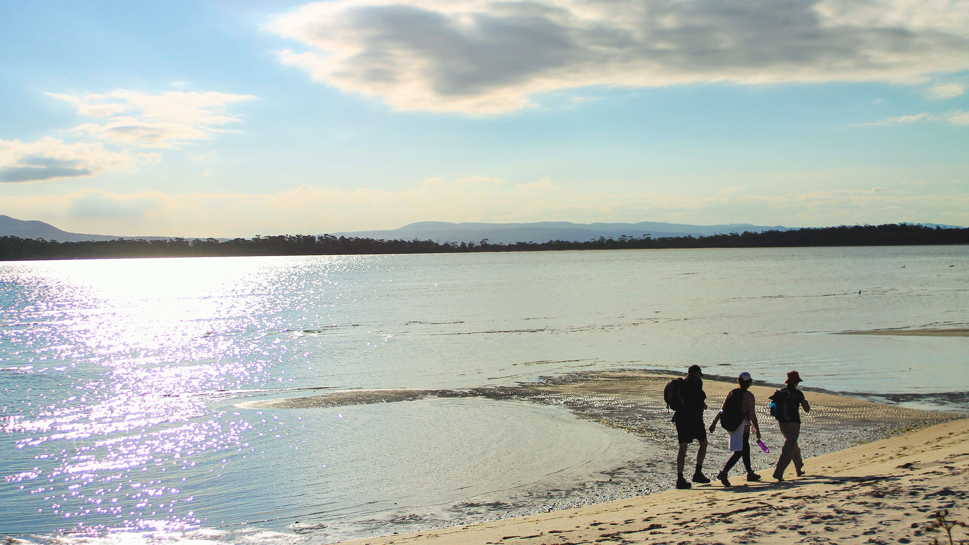 Beautiful view of Maria island with silhouette of people walking along the shore.
