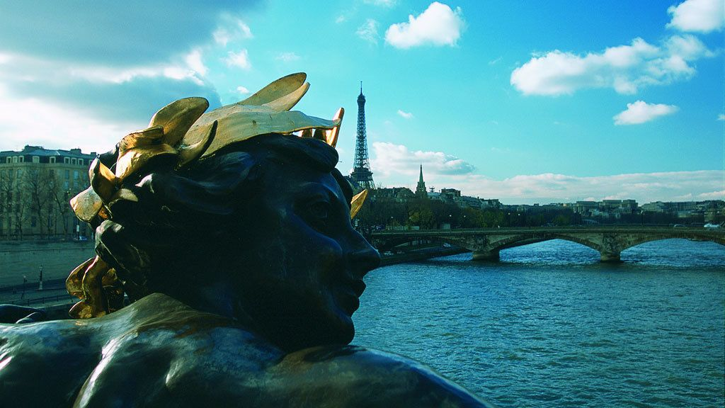 Statue with Alexandre III bridge and Eiffel tower in background in Paris