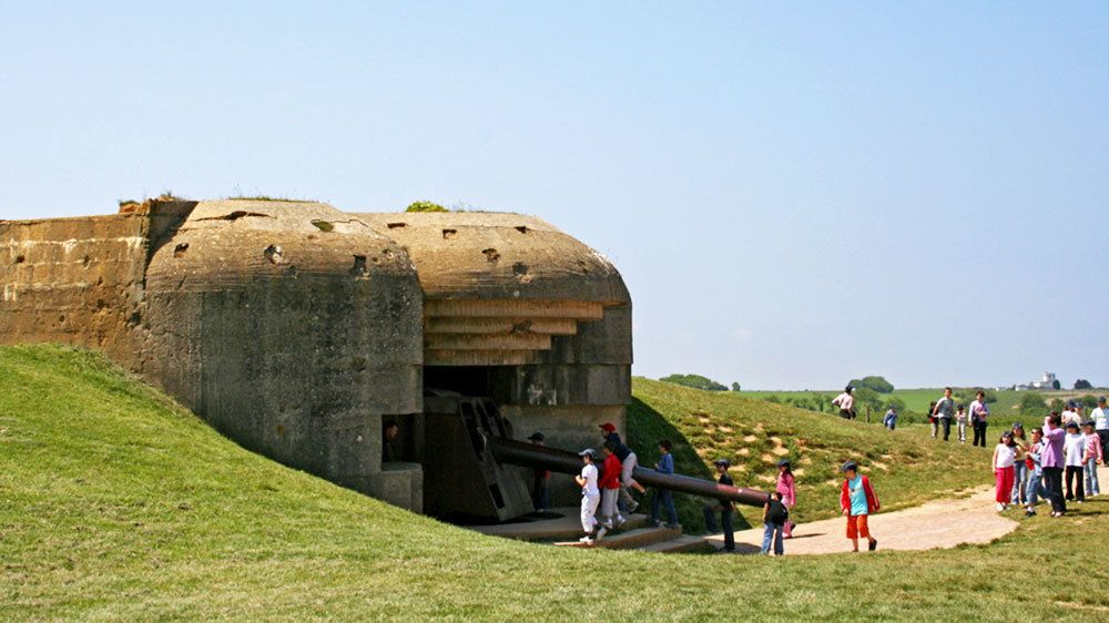 Tourists looking at old gun emplacement at beach in Normandy