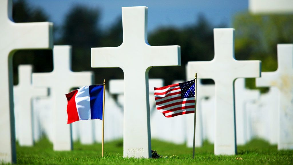 Crosses marking graves with flags in Normandy