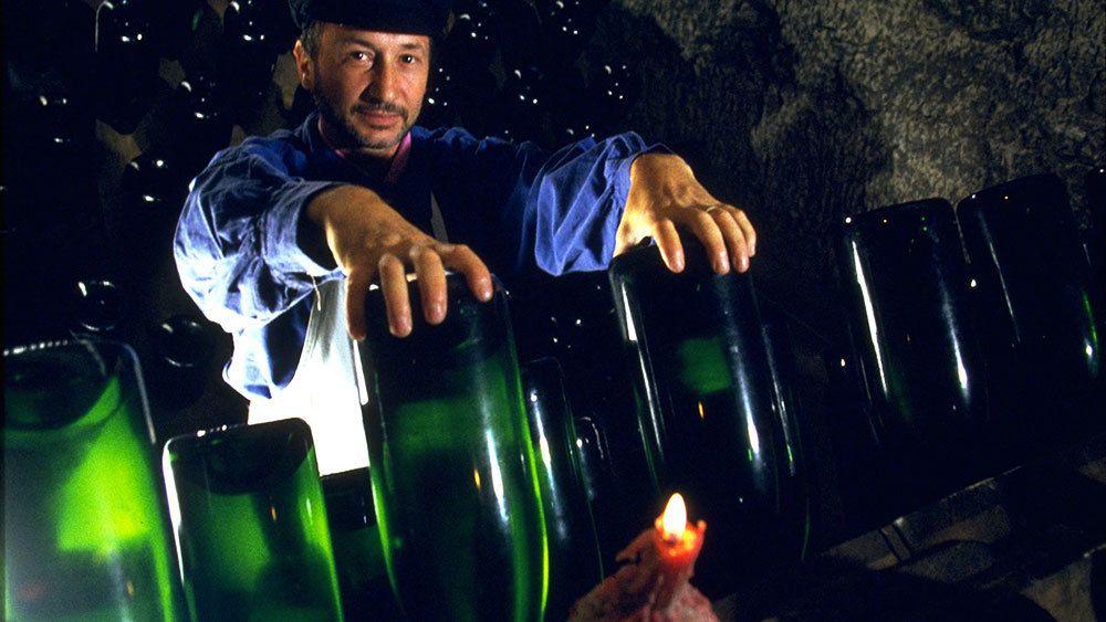 Man placing empty wine bottles in rack in Reims