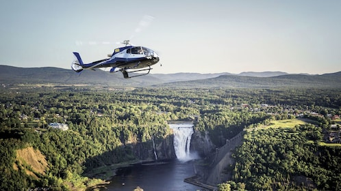 Helicopter over a waterfall surrounded by trees in Quebec