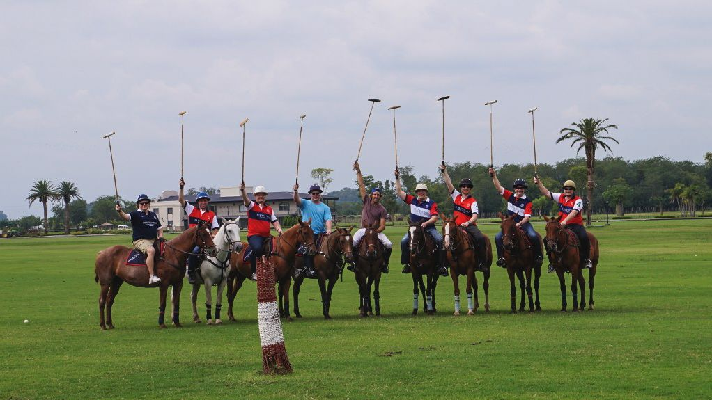 Several people on horses with polo sticks.