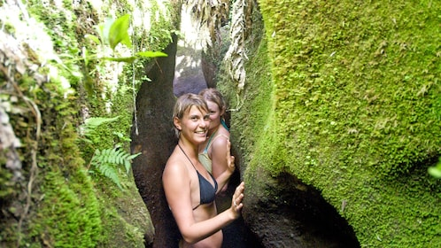 woman squeezing through narrow rock path in New Zealand