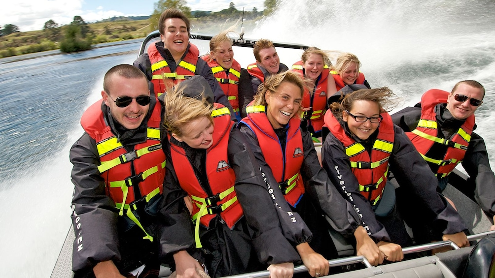 Show item 1 of 10. speedboat passengers holding on to railings in New Zealand