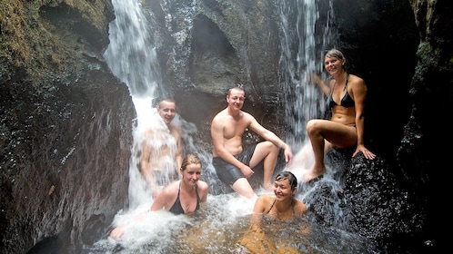 group sitting under a small waterfall in New Zealand